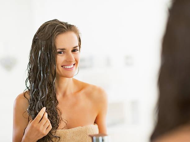 happy young woman applying hair mask in bathroom - 護髮用品 個照片及圖片檔