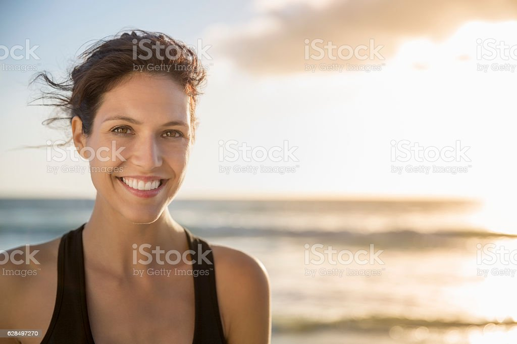 Happy young woman at beach during sunset stock photo