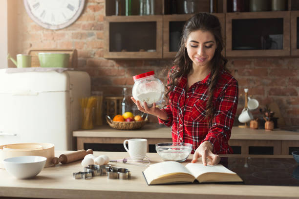 Happy young woman baking in loft kitchen stock photo