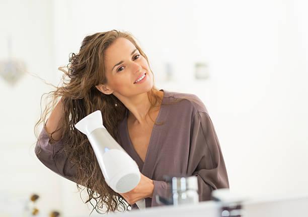glückliche junge frau blasen trocknen ihr haar im bad - haarfön stock-fotos und bilder