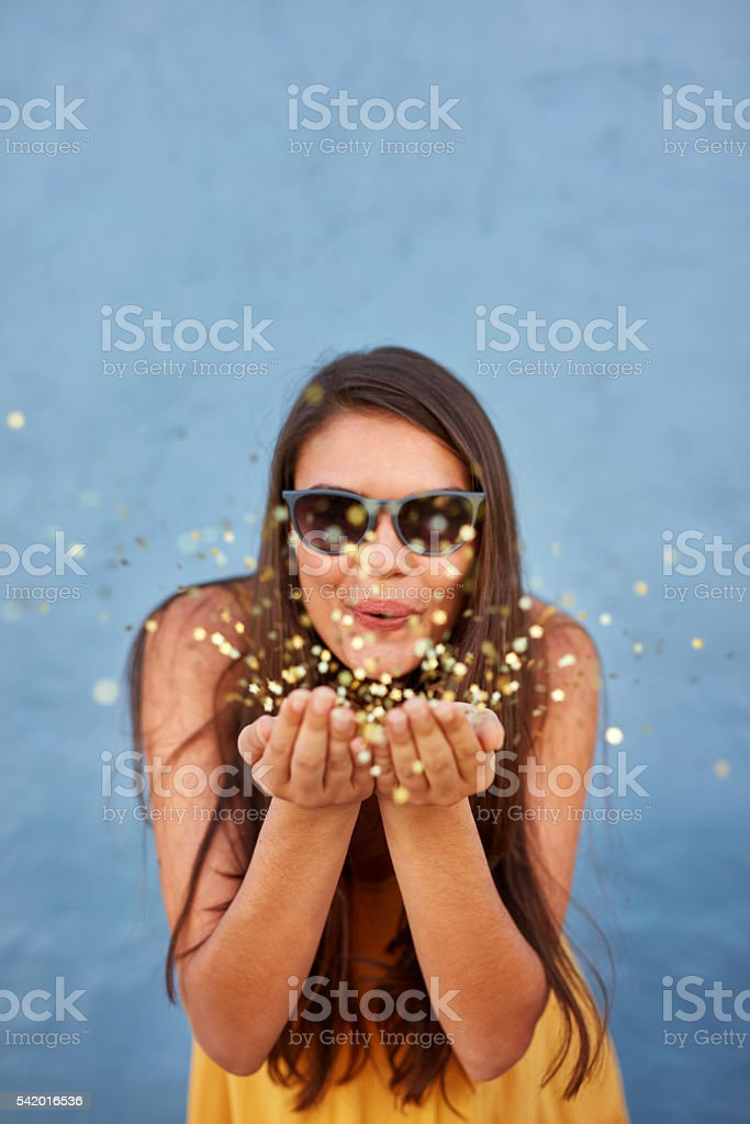 Happy young woman blowing confetti in the air stock photo