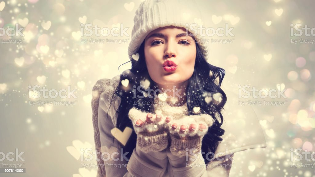 Happy young woman blowing snow and hearts stock photo