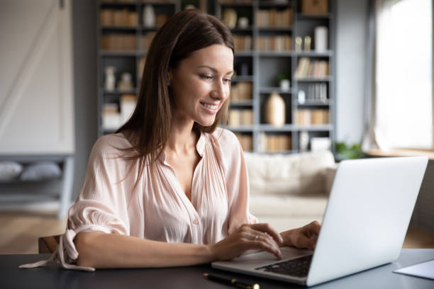 Happy young woman browsing internet on laptop stock photo