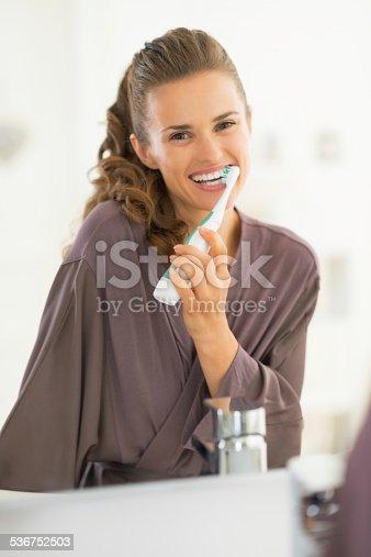 istock happy young woman brushing teeth in bathroom 536752503