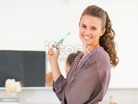 istock happy young woman brushing teeth in bathroom 536892513