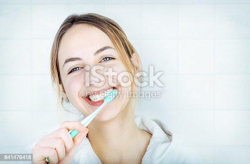 637874676istockphoto Happy young woman brushing teeth . 641476416