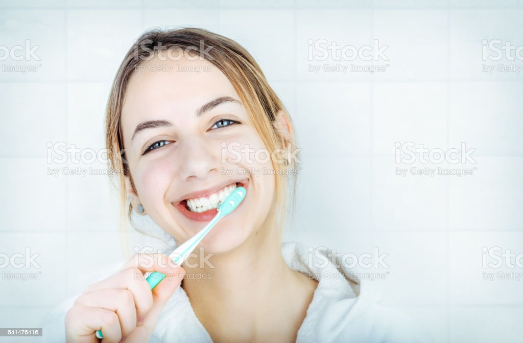 Happy young woman brushing teeth . stock photo