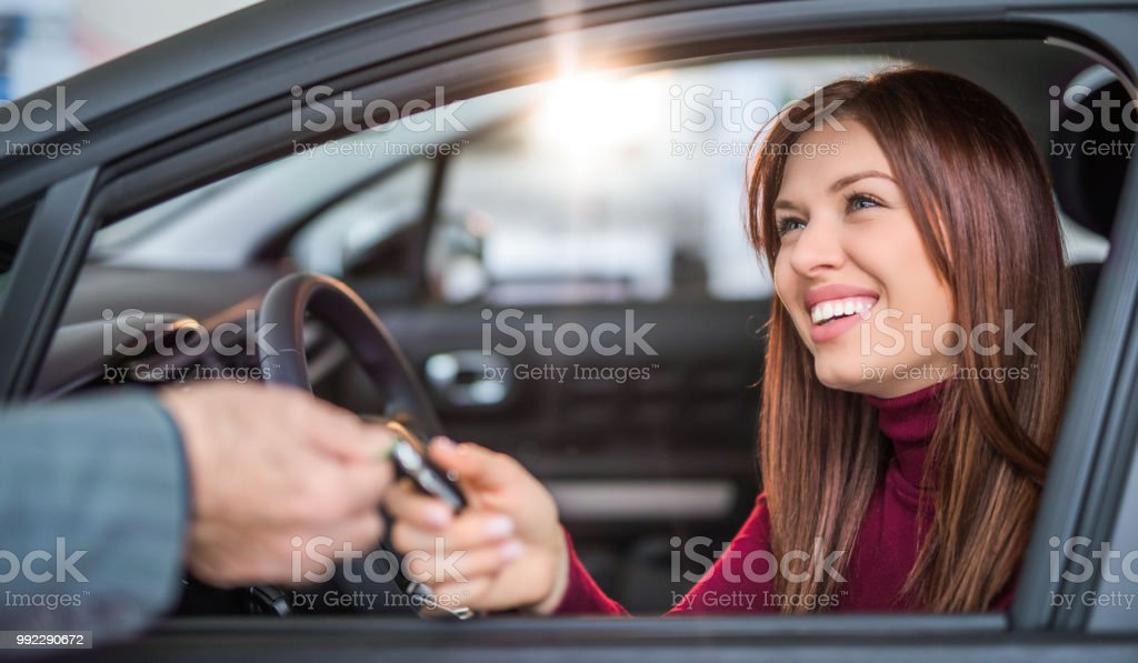Happy young woman buying her dream car. stock photo