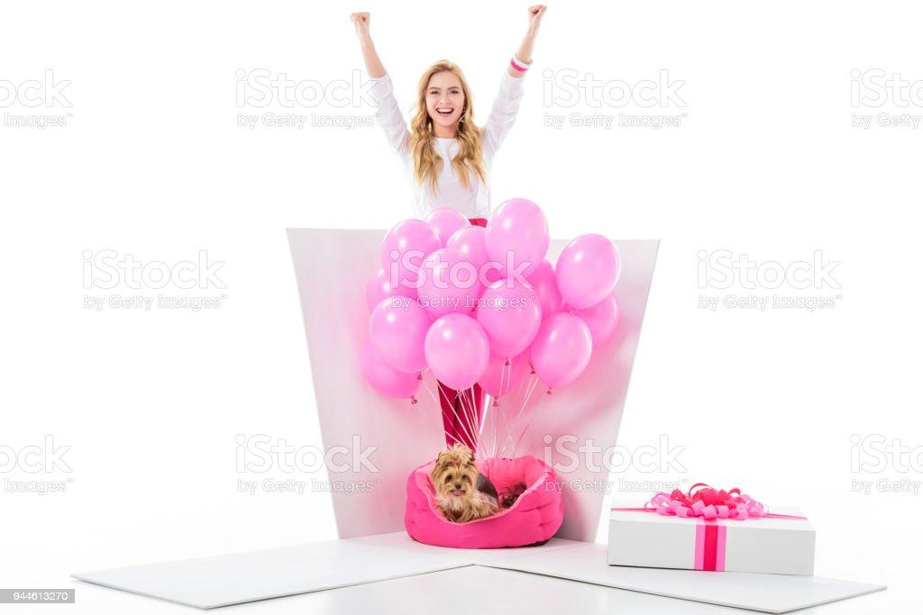 59b43ecbf Mujer joven feliz por caja de regalo con perro yorkie y globos color rosa  aislados en