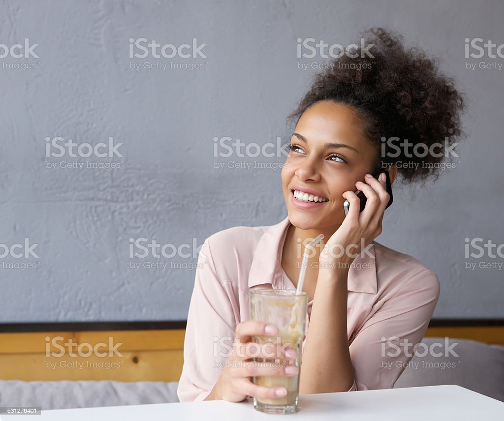Happy young woman calling by mobile phone stock photo