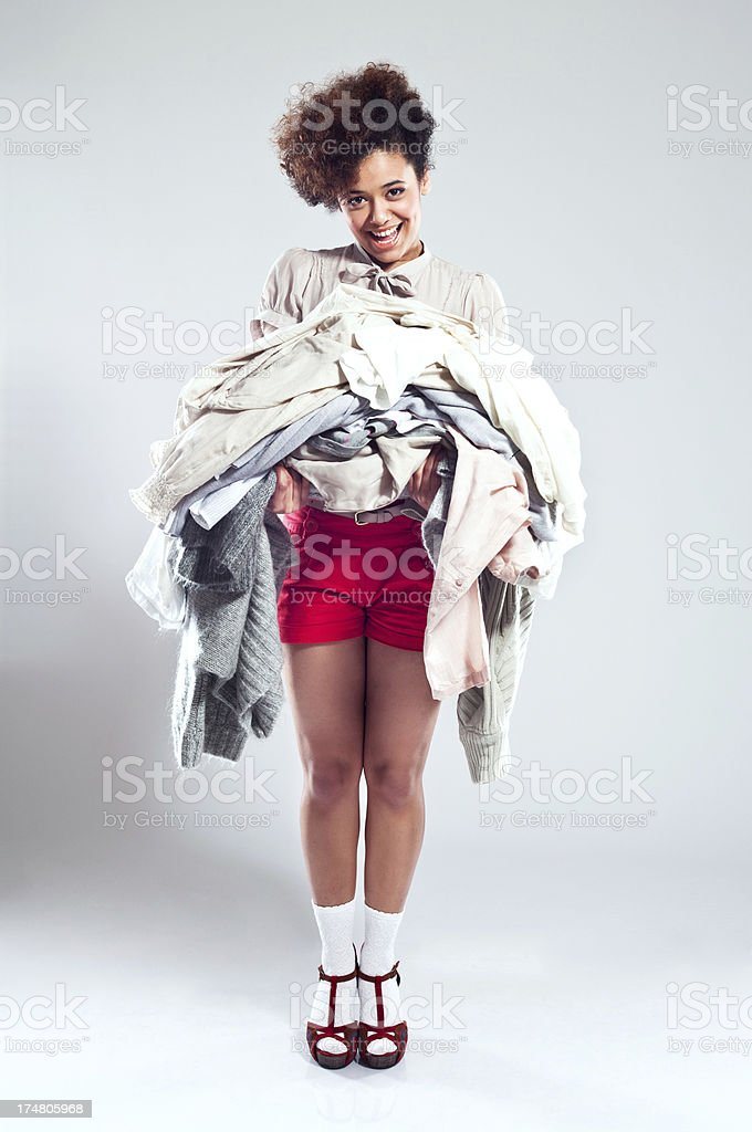 Happy Young Woman carrying clothes Portrait of beautiful teenaged afro girl carrying a pile of clothes and laughing at the camera. 18-19 Years Stock Photo