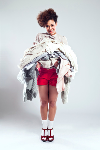 Happy Young Woman Carrying Clothes Stock Photo - Download Image Now