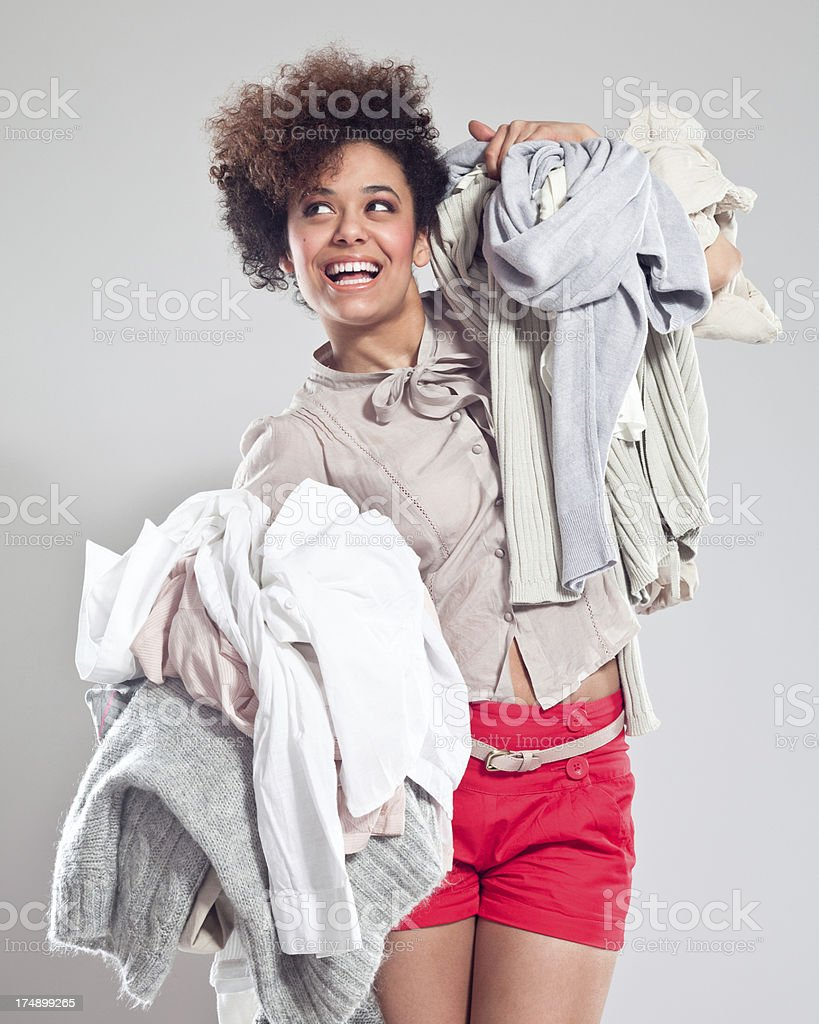 Happy Young Woman carrying clothes Portrait of beautiful teenaged afro girl carrying two piles of clothes in her hands, looking away and smiling. 18-19 Years Stock Photo