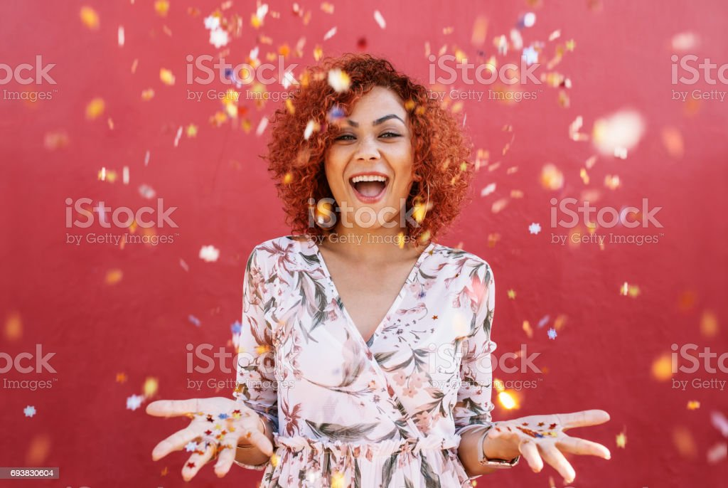 Happy young woman celebrating with confetti all around. stock photo