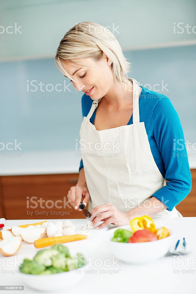 Happy, young woman chopping vegetables in the kitchen royalty-free stock photo