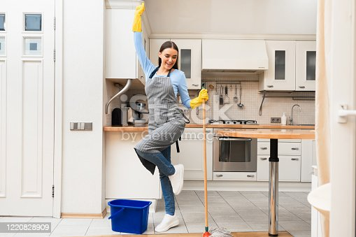1081403344 istock photo Happy young woman cleaning kitchen floor dancing with mop 1220828909