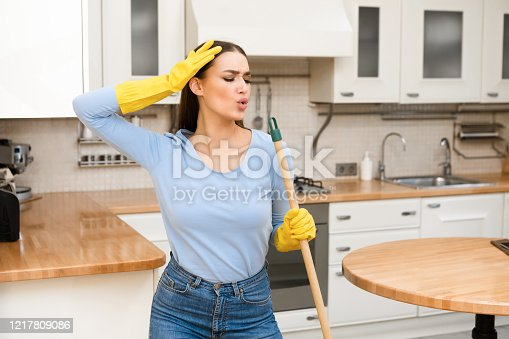 1081403344 istock photo Happy young woman cleaning kitchen floor singing at mop 1217809086