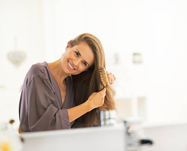 heureux jeune femme cheveux peignage - peigne photos et images de collection
