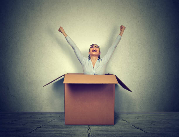 Happy young woman coming out from a small box Happy young woman coming out from a small box confined space stock pictures, royalty-free photos & images