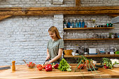 Happy young woman cooking delicious and healthy food in the loft kitchen at rustic apartment