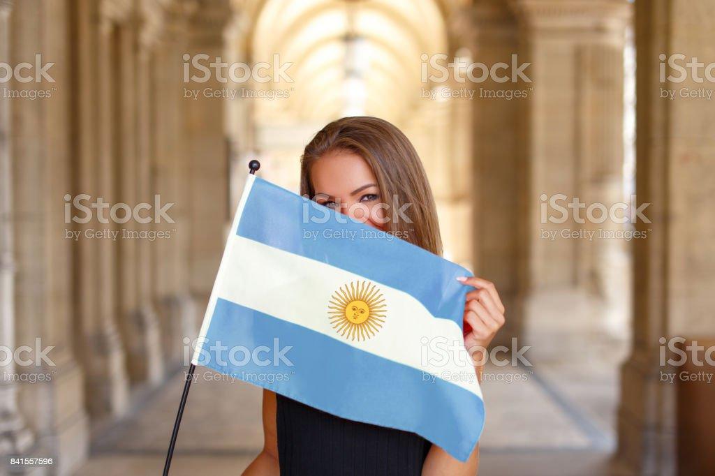 Mulher jovem feliz, cobrindo o rosto pela bandeira da Argentina - foto de acervo