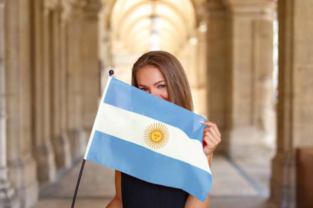 mulher jovem feliz, cobrindo o rosto pela bandeira da argentina - belas mulheres argentina - fotografias e filmes do acervo