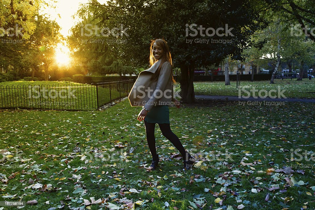 happy young woman dancing in park, autumn sunset royalty-free stock photo