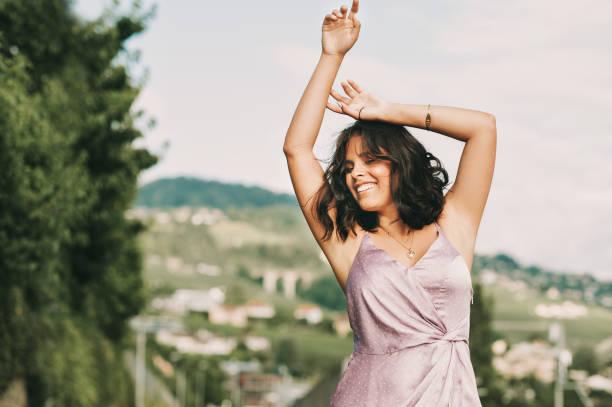Glückliche junge Frau tanzt auf der Straße, trägt lila Kleid, Glück und Freiheit – Foto