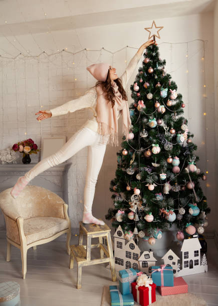 Happy young woman decorates the Christmas tree. A girl in a swea stock photo