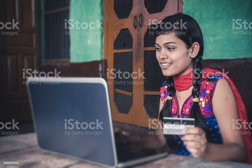 Happy young woman doing online shopping at home. stock photo