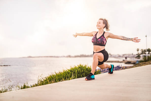 glückliche junge frau, die yoga neben dem meer auf einer zypern-insel macht. - ruhegebet tattoo stock-fotos und bilder