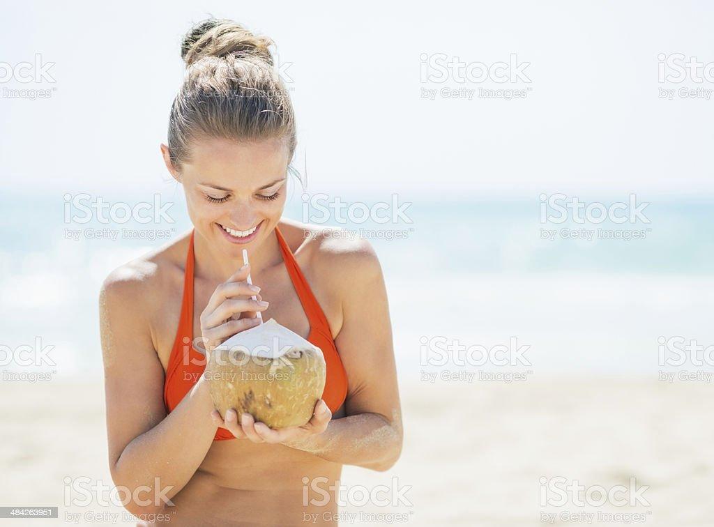Feliz Jovem mulher bebendo leite de coco na praia - foto de acervo