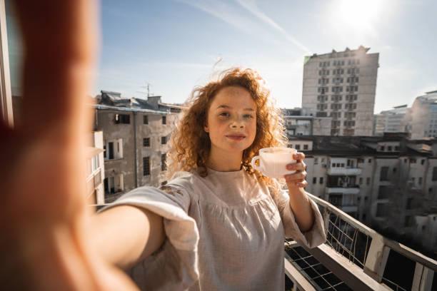 Glückliche junge Frau trinkt Kaffee und macht Selfie auf Balkon – Foto