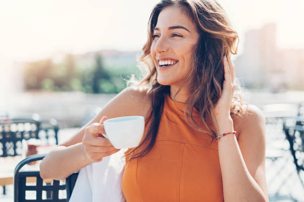 Happy young woman drinking coffee outdoors stock photo