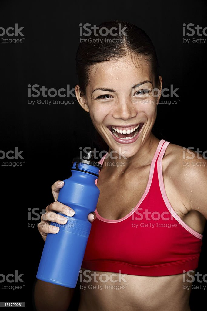 A happy young woman drinking from her bottle after workout royalty-free stock photo