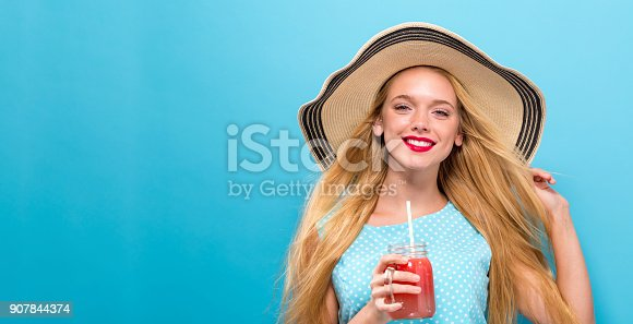 istock Happy young woman drinking smoothie 907844374