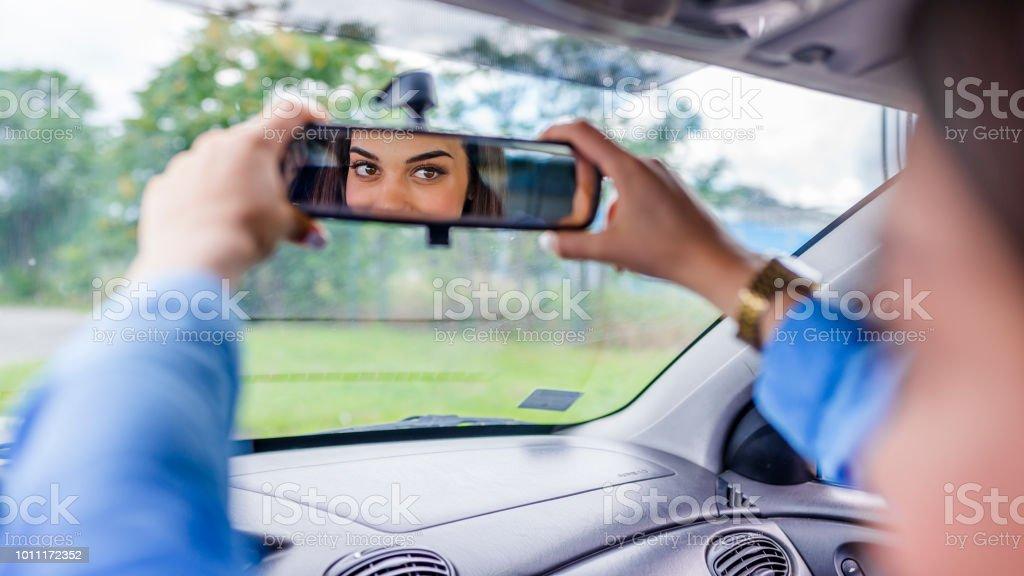 Motorista jovem feliz olhando ajuste espelho de vista traseira do carro - foto de acervo