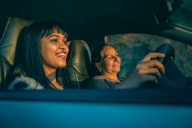 Happy young woman driving a car with her mother. stock photo