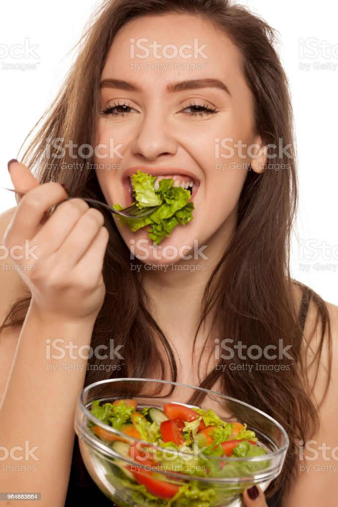 Happy young woman eat letuce salad on white background royalty-free stock photo