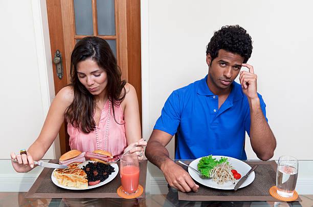 mujer joven feliz comer mucho. - ironía fotografías e imágenes de stock