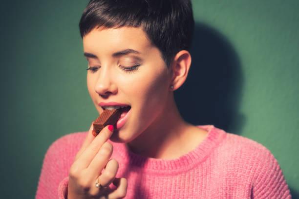 glückliche junge frau essen schoko-cookie - schokoladenplätzchen stock-fotos und bilder