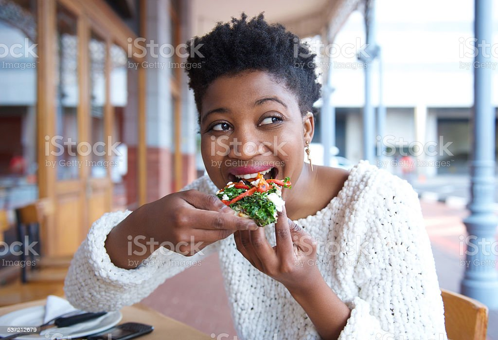 Happy young woman eating pizza at restaurant stock photo