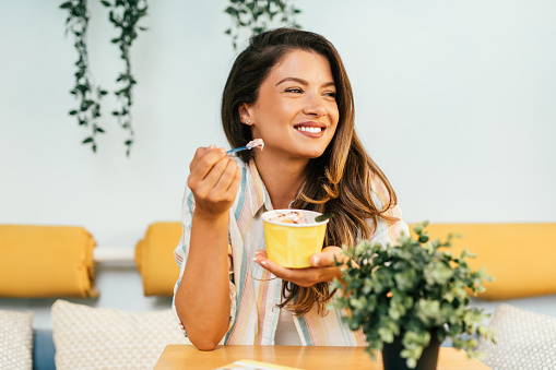Beautiful and happy brown hair woman enjoying in eating delicious handmade rolled ice cream.