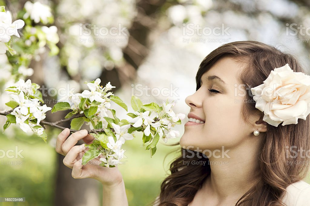 Happy young woman enjoying the fragrance of flowers royalty-free stock photo