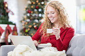 Happy young woman enjoys shopping online for Christmas presents