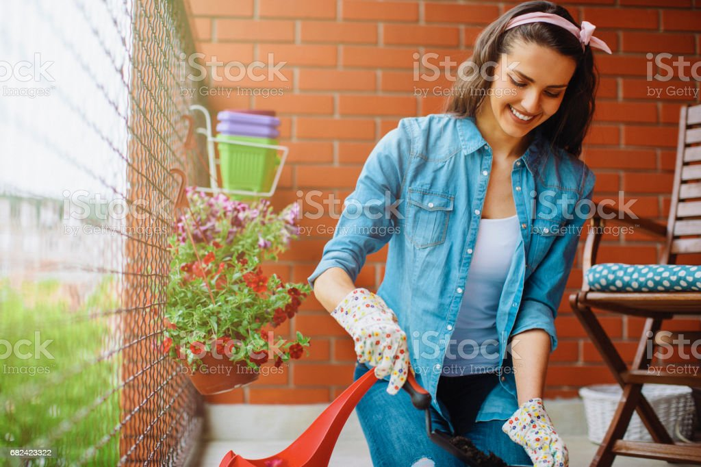 Happy young woman gardening on a balcony royalty-free stock photo