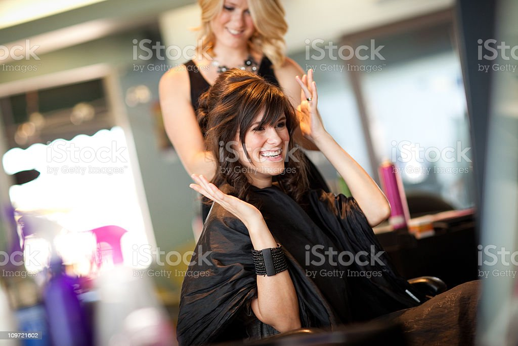 Happy Young Woman Getting Hair Styled as Updo in Salon stock photo
