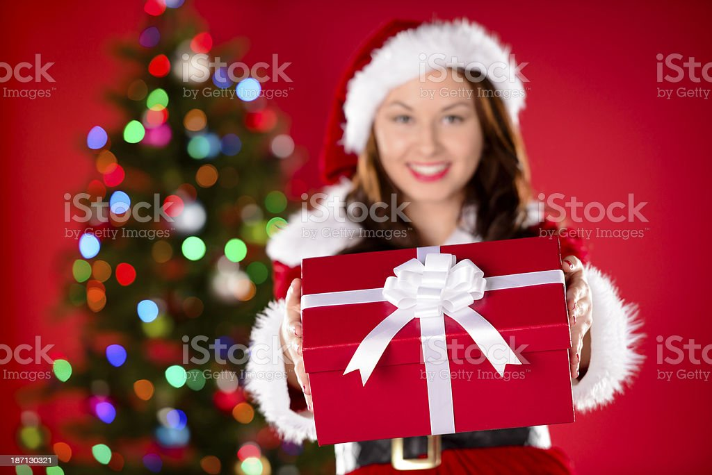 Happy young woman giving christmas present royalty-free stock photo