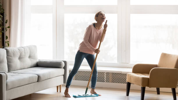 happy young woman have fun dancing cleaning home - sweeping stock pictures, royalty-free photos & images