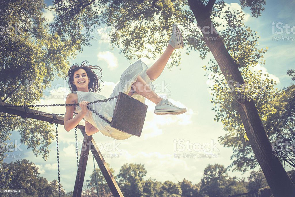 Happy young woman having fun on the swing stock photo